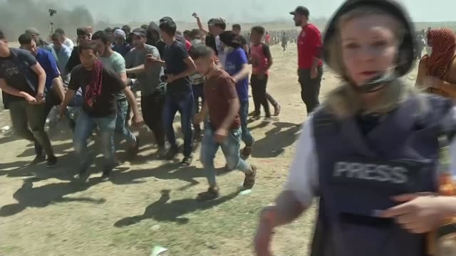 stockvideo's en b-roll-footage met israeli army open fire on palestinian protesters; israel / gaza border: ext wide shot palestinian demonstrators gathered as smoke rising in the air... - war and conflict