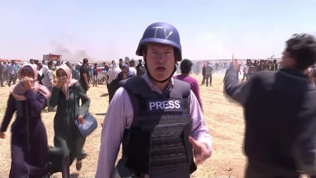 Israeli army open fire on Palestinian protesters TILT DOWN canisters dropped by drones Reporter to camera Palestinian protesters along including man...