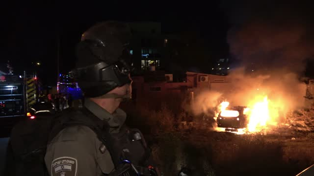 israeli border police stand guard as firefighters put out a burning car of jewish settlers that was set on fire by palestinians in the neighborhood... - burning stock videos & royalty-free footage