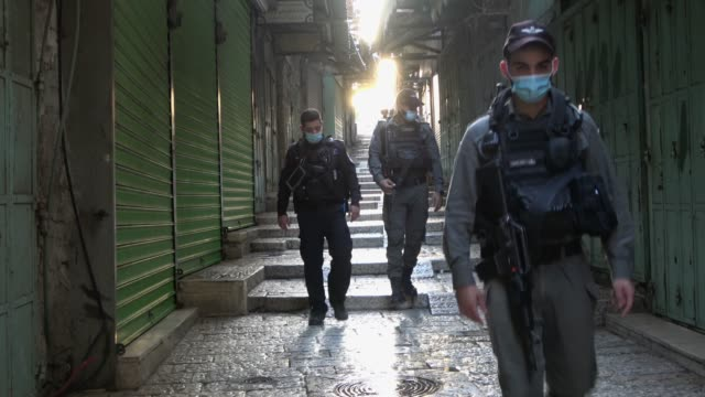 israeli border police wearing protective mask walk along empty alley lined with closed shops in the old city, amid new lock-down imposed due a spike... - israel stock videos & royalty-free footage