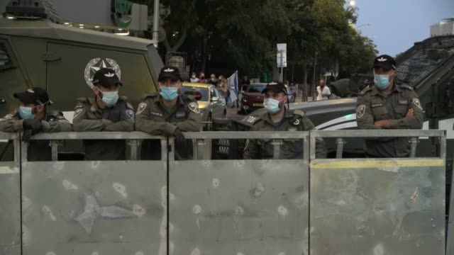 israeli border policemen stand behind barricade as at least 6000 demonstrators massed outside prime minister benjamin netanyahu's official residence... - バリケード点の映像素材/bロール