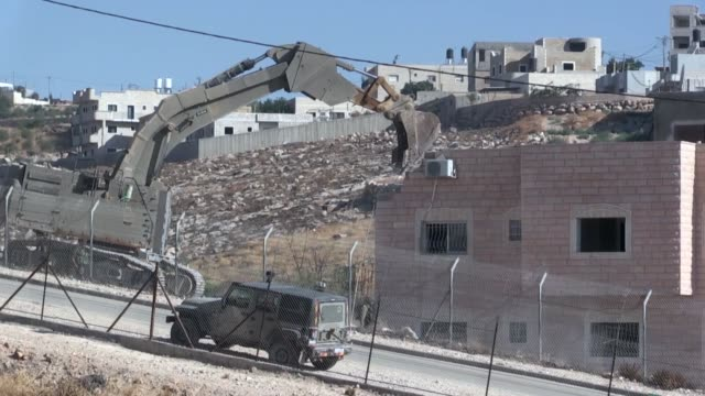 stockvideo's en b-roll-footage met israeli bulldozers backed by army forces demolish houses owned by palestinians in east jerusalem on july 22, 2019. palestinian akram zawahira whose... - nederzettingen