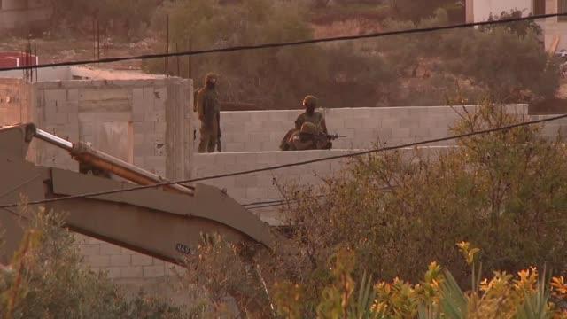 israeli bulldozers destroy the house of palestinian ashraf naalwa in shweika town of tulkarem west bank on december 17 2018 israeli forces on monday... - パレスチナ文化点の映像素材/bロール