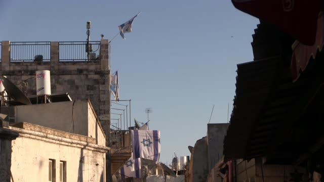 israeli flags hanging from a house which jewish settlers took over in el wad street also called by israelis haggai street in the muslim quarter, old... - gerusalemme est video stock e b–roll