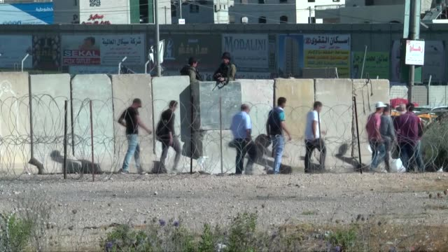 vídeos de stock, filmes e b-roll de israeli forces intervene the palestinian worshippers as they try to move for passing through the qalandiya checkpoint from ramallah into jerusalem... - ramallah