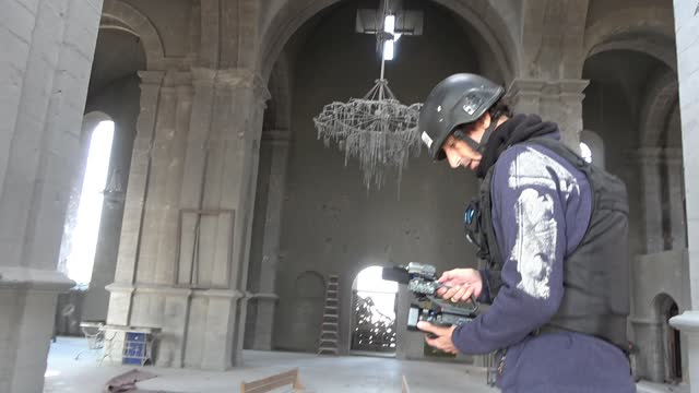 vidéos et rushes de israeli journalist itai anghel wearing helmet and protective flak jacket filming the damage inside the 19th-century holy savior cathedral, also known... - caméraman