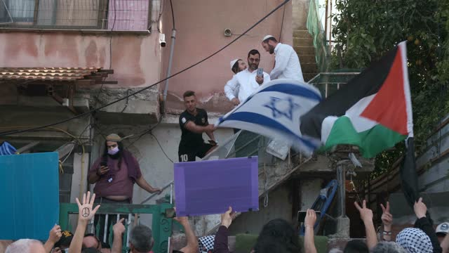 israeli left-wing activists and palestinians hold up placards and wave the palestinian flag in front of jewish settlers during a demonstration... - quarter stock videos & royalty-free footage