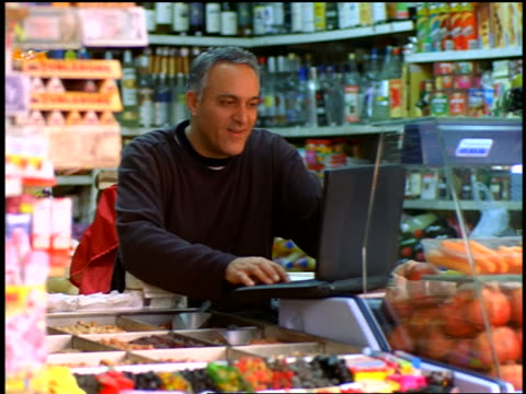 Israeli man typing on laptop in small grocery store / Tel Aviv