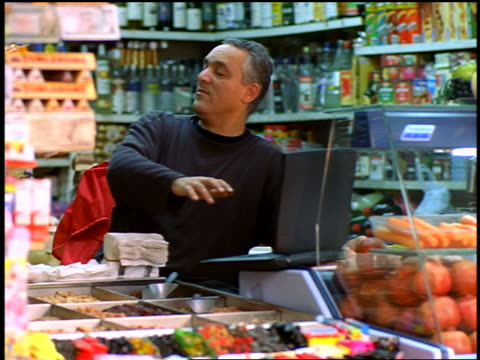 Israeli man using laptop in small grocery store / people passing in foreground / Tel Aviv