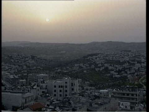israeli occupation continues itn israel west bank bethlehem ms sun rising tgv rooftops of bethlehem town at dawn tlms israeli troops along street... - church of the nativity stock videos and b-roll footage