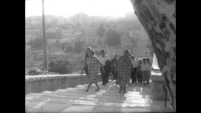 israeli pilgrims walk into jerusalem's old city / gather at the wailing wall / orthodox jews pray at wall / women watch the men pray from a distance. - 1967 stock videos & royalty-free footage