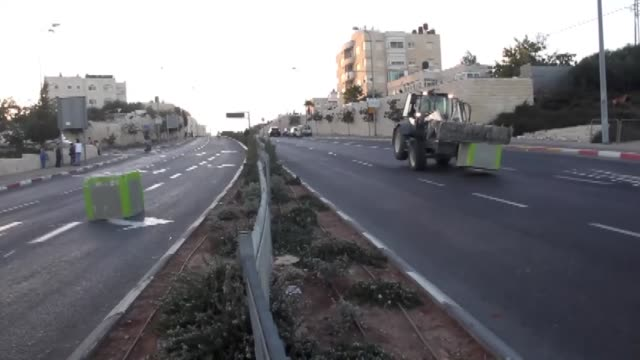 israeli policeman stand guard as cement blocks are placed by israeli security forces on a road linking the arab east jerusalem neighbourhood of beit... - ヨムキプール点の映像素材/bロール