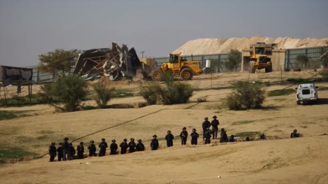 Israeli policemen stand guard as bulldozers demolish Palestinianowned homes in the Bedouin village of Umm alHiran in the Negev desert on January 18...