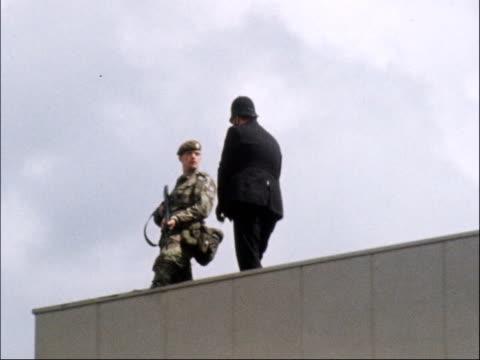 stockvideo's en b-roll-footage met israeli prime minister menachem begin arrives on uk visit; england: london airport: ext army tank along r-l soldier on roof joined by policeman car... - aan elkaar bevestigd