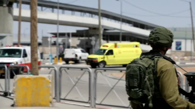 israeli security forces and ambulances gather at the site of a reported stabbing attack at the israeli-controlled qalandia checkpoint in the occupied... - israel stock videos & royalty-free footage