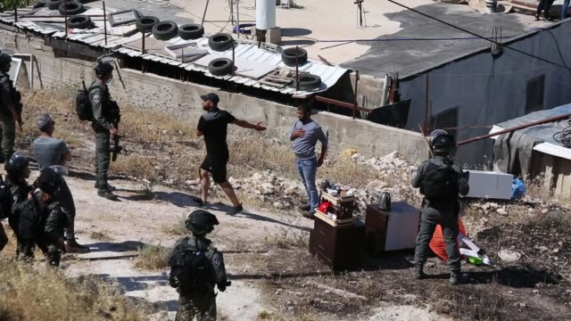israeli security forces stand guard at the area as municipal teams demolish the palestinian zaatre family's building with bulldozers after israeli... - gerusalemme est video stock e b–roll