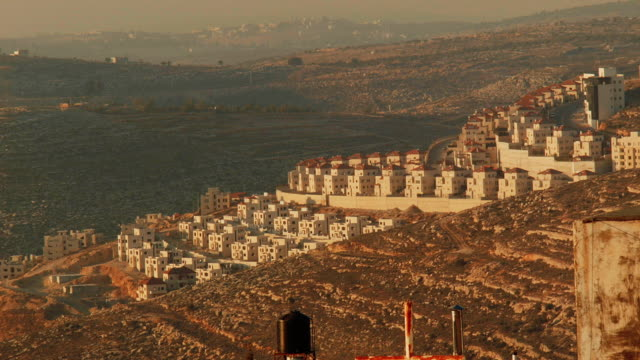 israeli settlement in the west bank in golden light, seen from ramallah. - spoonfilm stock-videos und b-roll-filmmaterial