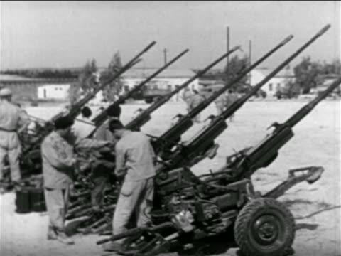 vídeos de stock, filmes e b-roll de israeli soldiers looking at line of antiaircraft guns outdoors / suez crisis / newsreel - 1956