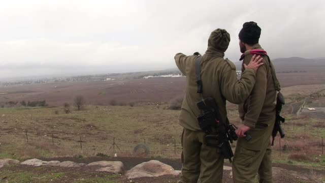 stockvideo's en b-roll-footage met israeli soldiers observing syria territory from ein zivan observation point near the strategic peak of mount bental and quneitra crossing border in... - israëlisch leger