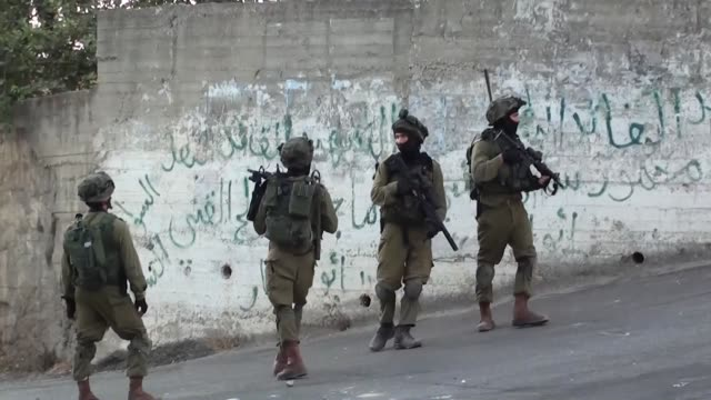 israeli soldiers patrol at a street, east of the west bank city of nablus, on october 3 as they search for the suspected palestinian killers of a... - イスラエルパレスチナ問題点の映像素材/bロール
