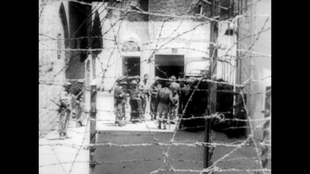 stockvideo's en b-roll-footage met / israeli soldiers push palestinian rebels out of haifa territory with force / soldiers walking through rumble and bombed out buildings / dead bodies... - 1948