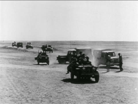 stockvideo's en b-roll-footage met israeli soldiers riding in offroad vehicle with trucks in background in desert / suez crisis - suezcrisis