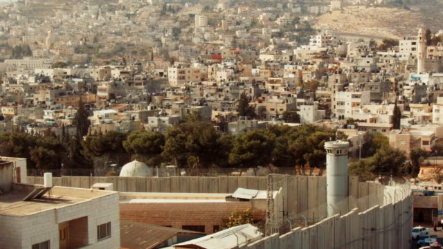 israeli west bank barrier and watch tower in front of residential district in bethlehem, palestine, middle east. - palestinian territories stock videos and b-roll footage