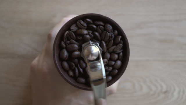 it grinds the coffee beans in a coffee mill - コーヒー豆点の映像素材/bロール
