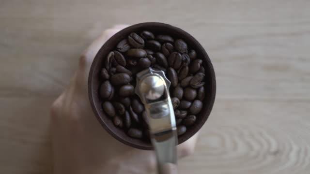 it grinds the coffee beans in a coffee mill - 挽く点の映像素材/bロール