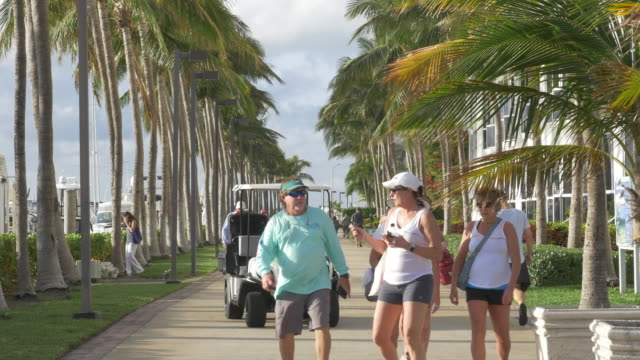 It is the travel season in Miami tourists walking to their hotel with their luggages transported by hotel staff behind them
