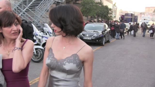 Italian actress Asia Argento comes out of Palais des festivals in Cannes poses for the fans and kisses on the lips a cameraman that she seems to know...