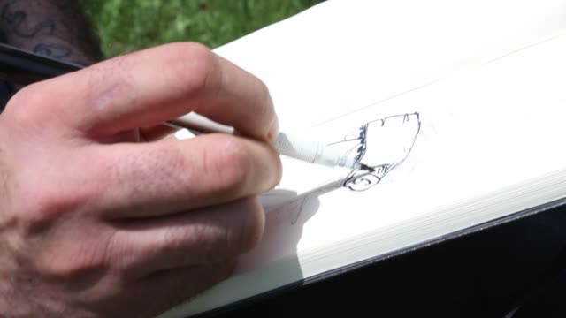 italian cartoonist cristian neri sits on a park bench and draws in a book a man wearing a protective mask on the top of his head on may 17, 2020 in... - カトゥーニスト点の映像素材/bロール