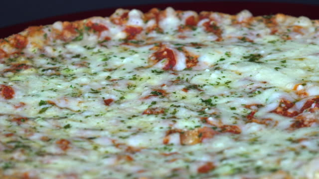 italian cuisine: thin crust cheese pizza turning on a food display - milchprodukte stock-videos und b-roll-filmmaterial