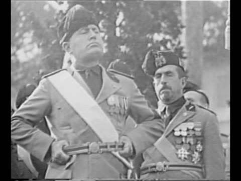 italian dictator benito mussolini speaks as his hands grasp the belt of his uniform other italian officials stand behind / side view crowd in piazza... - piazza venezia stock videos and b-roll footage