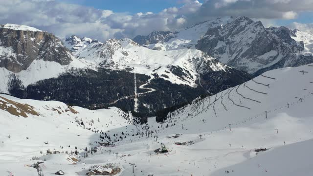 italian dolomites drone footage aerial in winter sunny day. panorama over the ski slopes and lifts in the ski area of canazei and compitello di fassa, trentino, italy - canazei video stock e b–roll