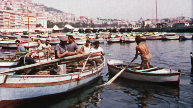 italian fishermen repair boats and nets in the warm summer sun of the amalfi coast, italy. - 1950 1959 stock-videos und b-roll-filmmaterial