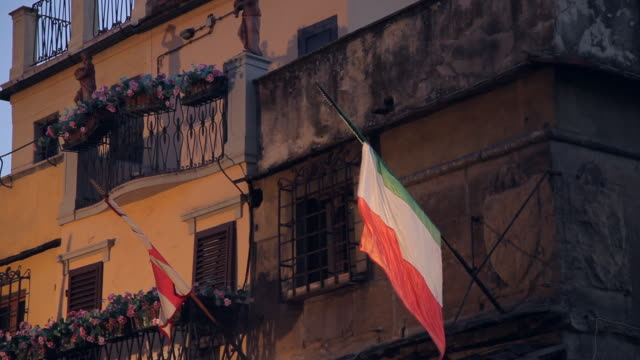 mh la ld italian flag hanging outside building / florence, italy - italienische flagge stock-videos und b-roll-filmmaterial