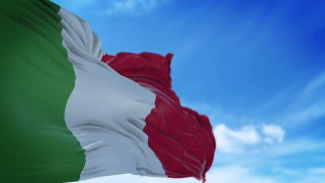italienische flagge weht langsam gegen blauen himmel in 4k-auflösung - italienische flagge stock-videos und b-roll-filmmaterial