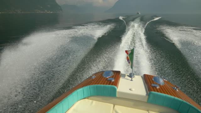 italian flag on a classic luxury wooden runabout boat on an italian lake. - 唯一点の映像素材/bロール