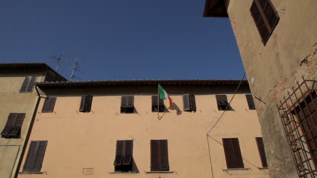 ws la ld italian flag on building / tuscany, italy - italienische flagge stock-videos und b-roll-filmmaterial
