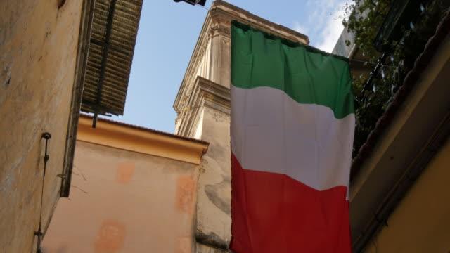 italian flag on narrow street, sorrento, costiera amalfitana (amalfi coast), unesco world heritage site, campania, italy, europe - bandiera nazionale video stock e b–roll