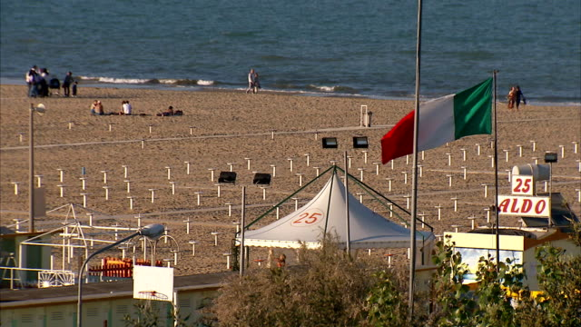 italian flag waves on rimini beach. - italien stock-videos und b-roll-filmmaterial