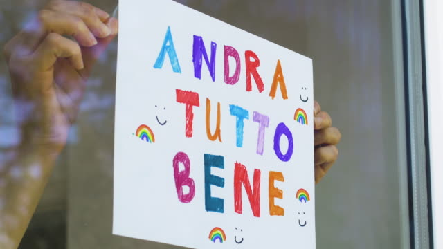italian language sign being placed in a window in response to the covid-19 virus emergency - quarantena video stock e b–roll