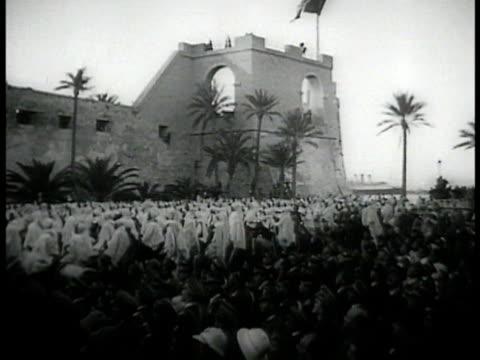 vídeos de stock, filmes e b-roll de italian mussolini flag ws libyans raising hands in crowd libya ms prime minister dictator of italy benito mussolini raising sword - benito mussolini