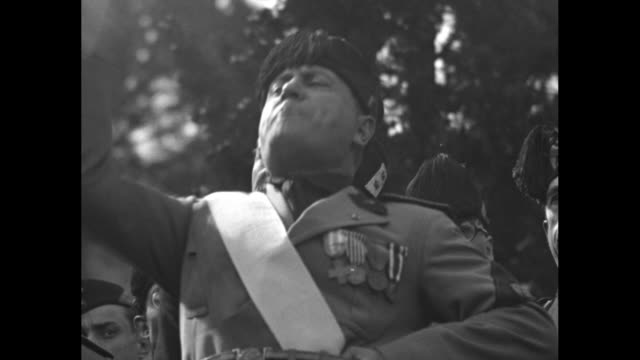 cu italian prime minister benito mussolini in uniform speaking in front of trees with other fascist officers behind him all give fascist salute /... - dictator stock videos & royalty-free footage
