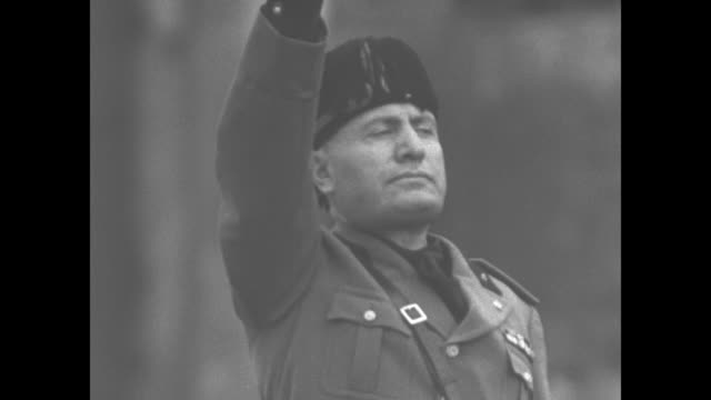 cu italian prime minister benito mussolini salutes as blur of troops march past him in foreground / ms mussolini on platform with military officers... - piazza venezia stock videos and b-roll footage