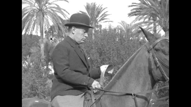 italian prime minister benito mussolini, wearing civilian clothing and a bowler hat, sits astride a horse in the time frame near his 46th birthday;... - benito mussolini stock videos & royalty-free footage