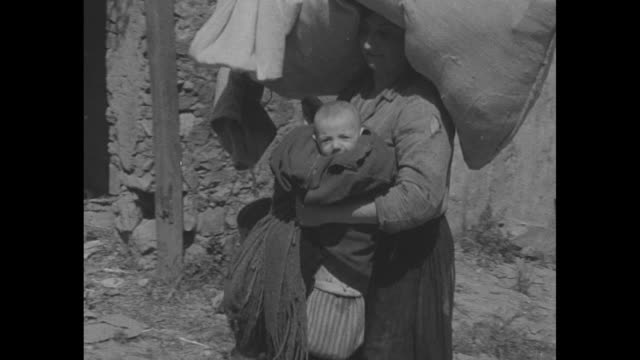 italian refugees primarily women and children crouch in front of wall / vs cu women babies children in refugee group / soldier helps very old woman... - old prisoner stock videos & royalty-free footage
