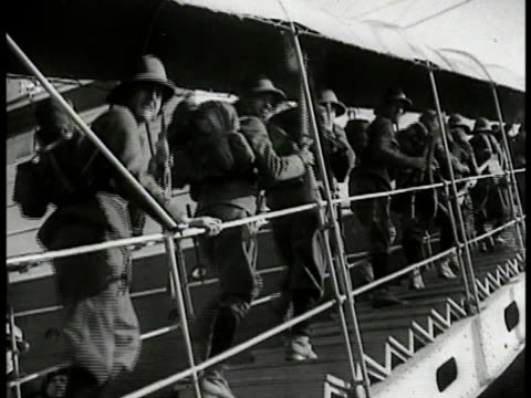stockvideo's en b-roll-footage met italian soldiers boarding walking up ship ramp italian troops crowded on ship's deck two ships on suez canal. - 1935