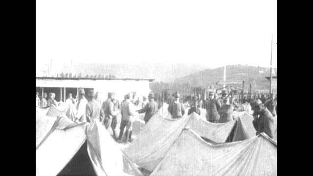 italian soldiers on the carso front walk toward camera with captured austrian soldier prisoners during world war i / pan prison camp with rows of... - austria video stock e b–roll